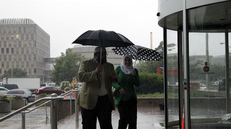 Mohamed El-Filali, left, of Paterson, N.J. hurries in the rain with Nadia Kahf,  attorney with the Council on American-Islamic Relations in New Jersey as they head to a meeting with New Jersey Attorney General Jeffrey S. Chiesa and Muslim leaders in Trenton, N.J., Thursday, May 24, 2012 . Following a three-month review, Gov. Chris Christie's administration said Thursday that New York City police did not violate New Jersey laws when they conducted surveillance of Muslim businesses, mosques and student groups, rejecting demands by Muslim leaders for a formal investigation and a clampdown on cross-border police operations.  (AP Photo/MelEvans)s