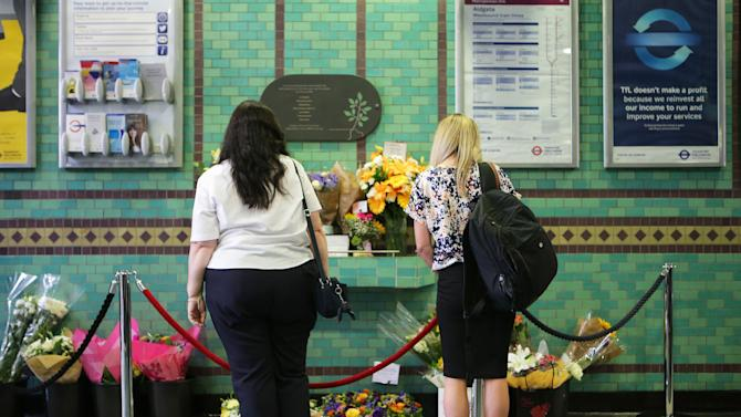 People look at flowers left by the July 7 memorial plaque at Aldgate Station, London, which names those who were killed in the bombings at the station, in 2005, on Tuesday July 7, 2015. Britons marked the 10th anniversary of the suicide bomb attacks on London's transit system Tuesday July 7, 2015,  when four British men inspired by al-Qaida blew themselves up on three London subway trains and a bus during the morning rush hour on July 7, 2005, killing 52 commuters.(Stefan Rousseau/PA via AP) UNITED KINGDOM OUT