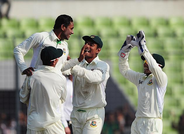 Bangladesh cricketer Sohag Gazi (L) celebrates with teammates the dismissal of West Indies cricketer Kieran Powell during the first day of the first Test match between Bangladesh and West Indies at th