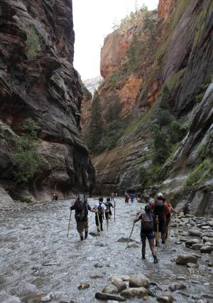 """FILE - In this Sept., 5, 2009, file photo, hikers wade through the cold Virgin River along the """"Narrows,"""" in Zion National Park, Utah. A 34-year-old man was found dead on Sunday, Sept. 28, 2014, in Zion National Park after rising floodwaters trapped him in a narrow canyon that is home to one of the park's best-known hiking trails. (AP Photo/Ross D. Franklin, File)"""