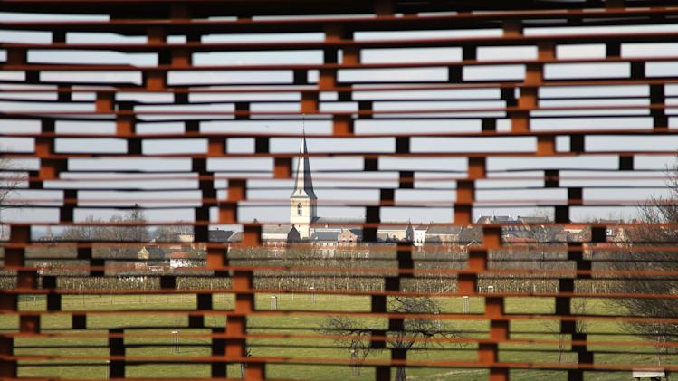 In this Feb. 20, 2013 file photo, a church is pictured through the steel layers of a see-through church on a hilltop in Borgloon, 80 km (50 miles) East of Brussels. The artistic vision of the church is made of rusty steel beams separated by gaps, and its austere beauty won it an international architecture prize. Yet the eerie desolation of the see-through installation has also turned into a reflection on the state of Roman Catholicism on a religion-weary continent where real churches, like the dozen dotting the hills of this verdant area, increasingly lose their flock and function. (AP Photo/Yves Logghe, file)