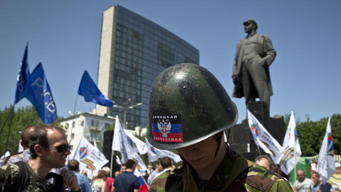 FILE - This, Sunday, May 18, 2014, file photo shows a pro-Russian youngster looking down while standing in a crowd control line during a rally by pro-Russian people in Lenin Square, in Donetsk, Ukraine. In the streets of Donetsk, the separatist leaders and their followers are increasingly derided as a collection of heavily armed, barely employed misfits. Outside of the rebels' headquarters, it can be difficult to find anyone who agrees with their calls to secede from Ukraine and link this part of the country — with its generations of ethnic and linguistic ties to Russia — to Moscow.(AP Photo/Vadim Ghirda, File)