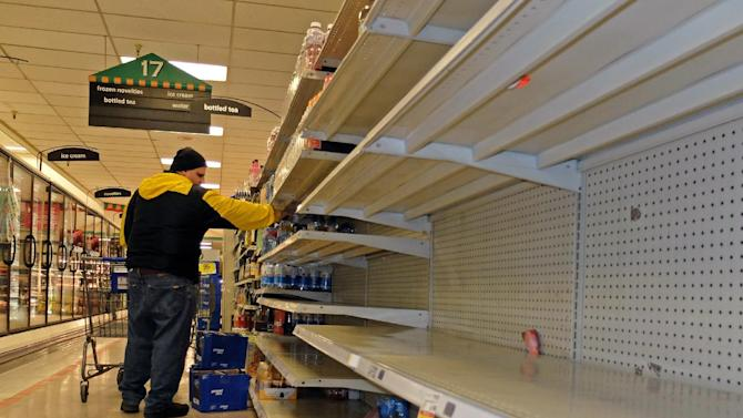 Jim Cole of Exeter, N.H., got the last few bottles of water at the Kroger in South Charleston W.Va. following a chemical spill on the Elk River that compromised the public water supply to eight counties of Thursday, Jan. 9, 2014. (AP Photo/Tyler Evert)