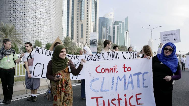 """Qatari Women activists holding a banner reading """"commit to climate justice 4 all """" as they march with local and international activists march to demand urgent action to address climate change at the U.N. climate talks in Doha, Qatar, Saturday , Dec. 1, 2012. (AP Photo/Osama Faisal)"""