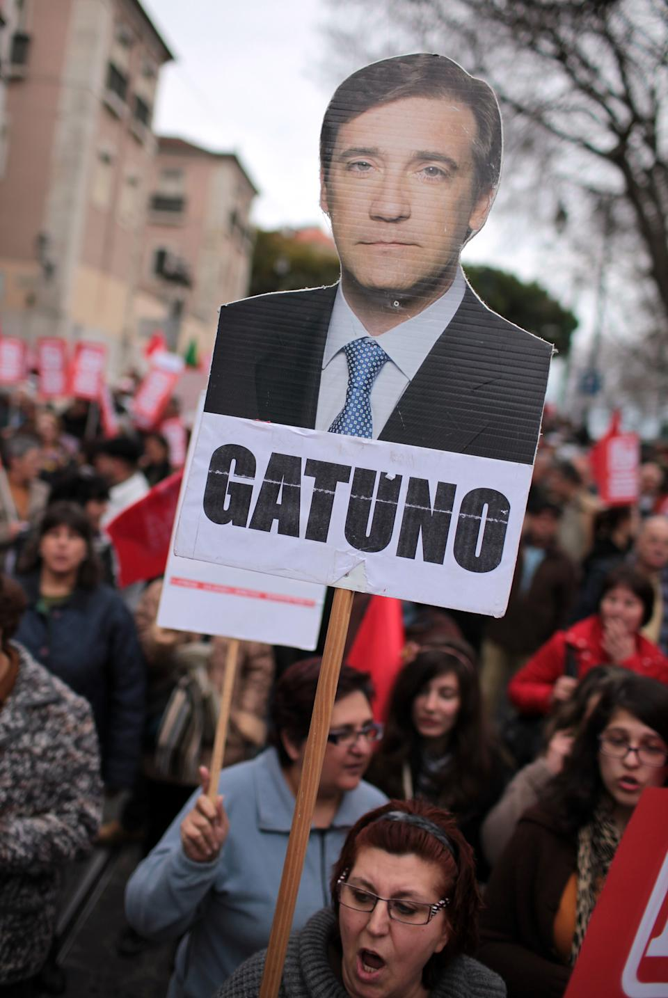 "A demonstrator carries a photo of Portuguese Prime Minister Pedro Passos Coelho with the label ""thief"" during an anti-austerity protest march in Lisbon Saturday, Feb. 16 2013. The protest was called by CGTP, the Portuguese confederation of workers unions. (AP Photo/Armando Franca)"