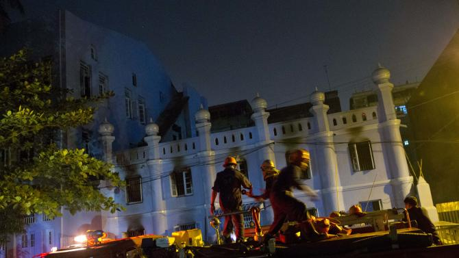Fire fighters walk outside of a mosque that a fire killed 13-children in Yangon, Myanmar, Tuesday, April 2, 2013. Police in Myanmar said 13 children died when an electrical fire broke out at the mosque in the country's largest city. (AP Photo/Gemunu Amarasinghe)