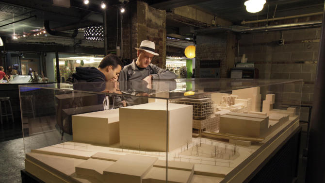 In this May 15, 2012 photo, visitors examine a model of the proposed expansion of the Chelsea Market in New York. One hundred years after the introduction of the Oreo, the complex that was once the former home to Nabisco is slated for an expansion many neighborhood residents oppose. (AP Photo/Richard Drew)