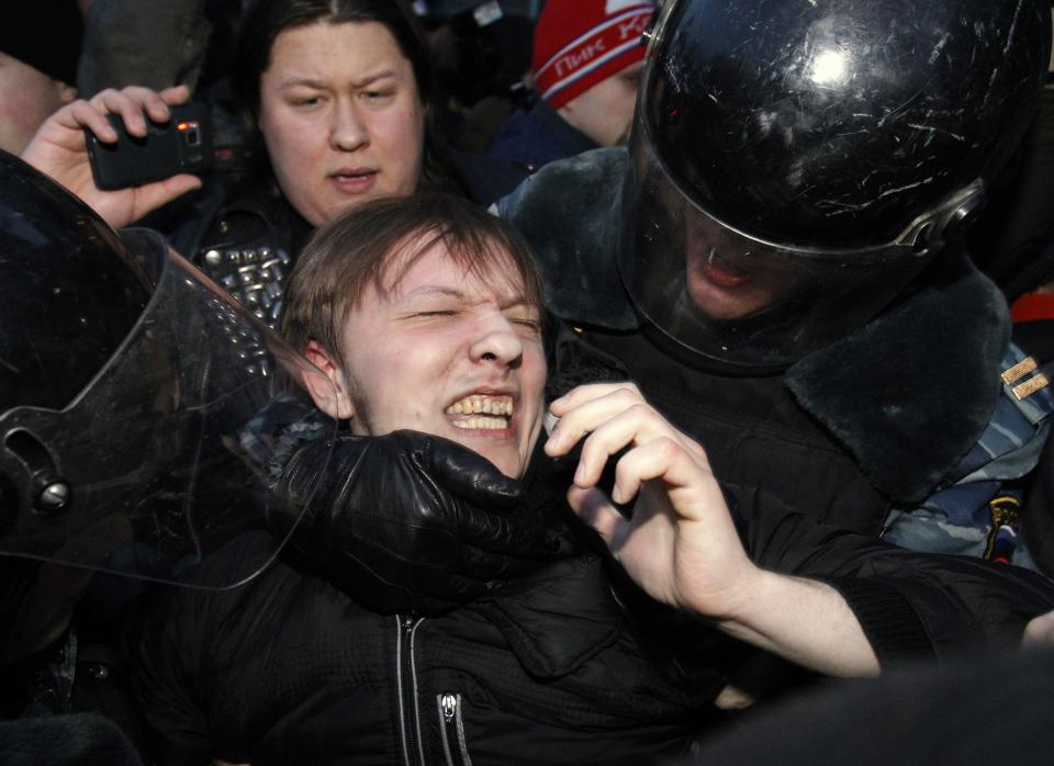 Russian police officers detain an opposition protester during a protest near the Central Election Committee in Moscow, Monday, March 5, 2012. Demonstrators are contesting the outcome of the vote, pointing to a campaign heavily slanted in Putin's favor and to reports of widespread violations in Sunday's ballot. (AP Photo/Ivan Sekretarev)