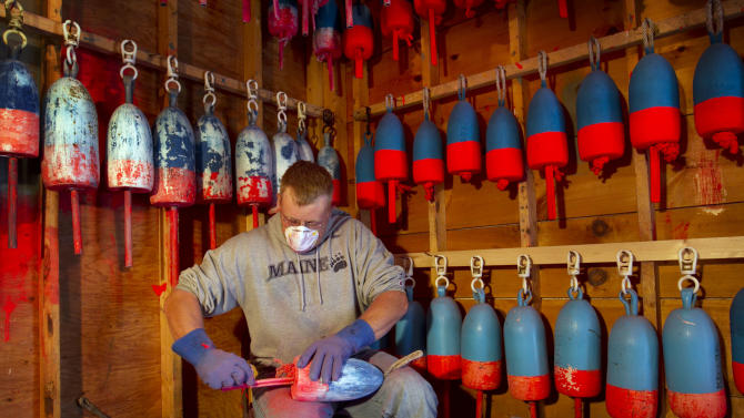 Lobsterman Kendall Delano sands last year's paint off lobster buoys he's painting in his workshop in Friendship, Maine, Thursday, May 10, 2012. Two lobster boats were recently sunk by vandals on Friendship, bringing back memories of territorial tensions in the industry that led to a shooting two summers ago. (AP Photo/Robert F. Bukaty)