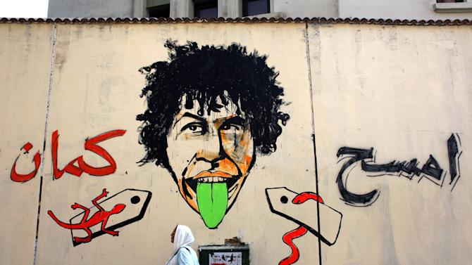 """A veiled Egyptian woman walks past newly painted graffiti that reads in Arabic """"erase more,"""" on a wall that was whitewashed during a cleanup campaign to erase old murals, in Tahrir Square, Cairo, Egypt, Wednesday, Sept. 19, 2012. Graffiti artists are repainting the walls in Mohammed Mahmoud Street, off Tahrir square, soon after municipal workers have whitewashed over a mural depicting the faces of victims of police brutality and violence over the past two years. (AP Photo/Nasser Nasser)"""