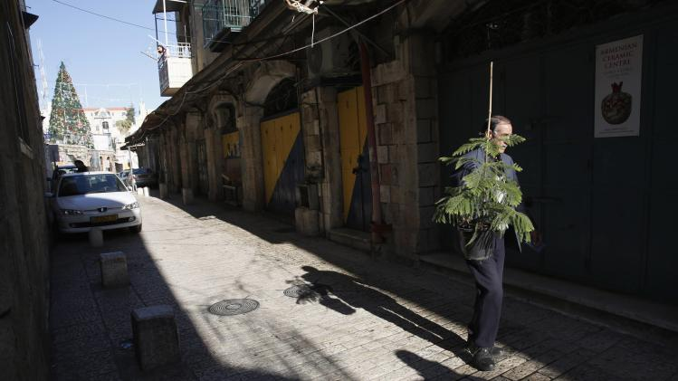 A man carries Christmas tree distributed by Jerusalem municipality in Jerusalem's Old City