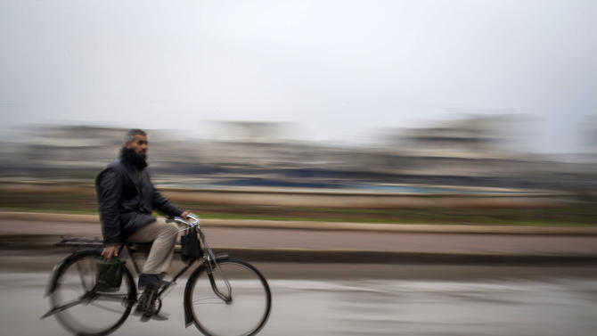 A man is rides a bicycle to carry gasoline in Aleppo, Syria, Saturday, Jan. 5, 2013. The revolt against President Bashar Assad that started in March 2011 began with peaceful protests but morphed into a civil war that has killed more than 60,000 people, according to a recent United Nations recent estimate. (AP Photo/ Andoni Lubaki)