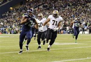 Seattle Seahawks defensive end Michael Bennett runs the ball in for a touchdown during the 1st quarter at CenturyLink Field in Seattle