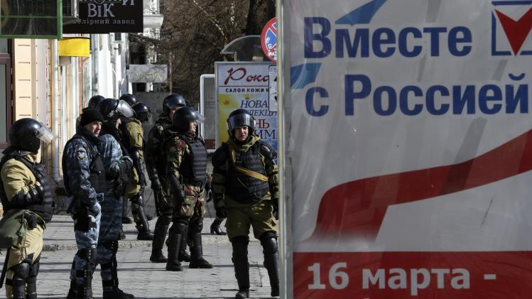 Members of a Crimean self-defence patrol near a referendum poster on a street in Simferopol