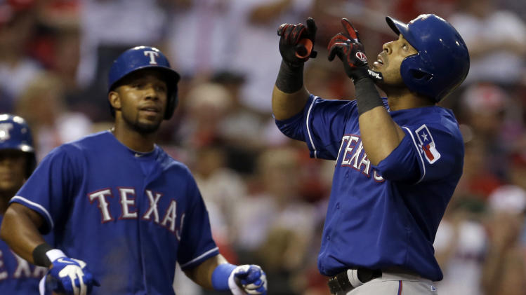 Texas Rangers' Nelson Cruz, right, points skyward after driving in teammate Elvis Andrus, left, on a two-run home run during the third inning of a baseball game against the St. Louis Cardinals on Saturday, June 22, 2013, in St. Louis. (AP Photo/Jeff Roberson)