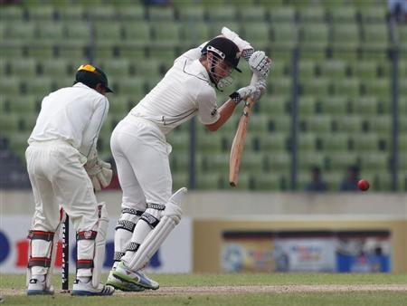 New Zealand's Kane Williamson plays a ball as Bangladesh's captain and wicket keeper Mushfiqur Rahim watches in Dhaka