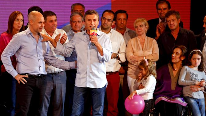 Macri, Buenos Aires' City Mayor and presidential candidate for PRO party, speaks as he embraces Rodriguez Larreta as Michetti, who lost in the primary election for Buenos Aires' Mayor, watches in Buenos Aires