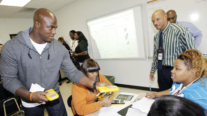 Dallas defensive lineman DeMarcus Ware hands out TI-84 calculators to a Lancaster High School Algebra II class powered by four Duracell AAA batteries during the Duracell Trust Your Power NFL Campaign event on Tuesday, Nov. 13, 2012inLancaster, Texas. (Photo by Brandon Wade/Invision for Duracell/AP Images)