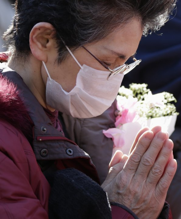 Woman takes part in a moment of silence to mark the second-year anniversary of the March 11, 2011 earthquake during a rally in Tokyo