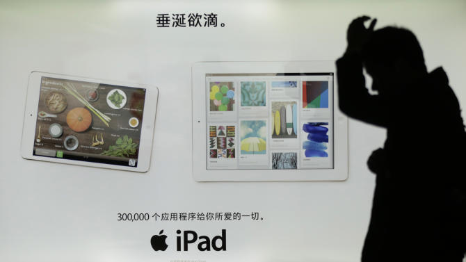 A man walks by an advertisement of Apple's iPad in Shanghai, China, Tuesday April 2, 2013. Apple apologized to Chinese consumers after government media attacked its repair policies for two weeks in a campaign that reeked of economic nationalism. Chinese on top reads; Drooling over it. (AP Photo/Eugene Hoshiko)