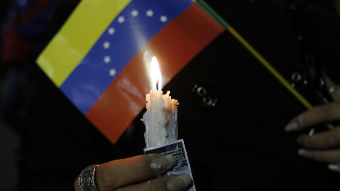 A person holds a candle and a Venezuelan flag during a vigil for Venezuela's President Hugo Chavez in La Paz, Bolivia, Monday Dec. 10, 2012. Chavez's cancer relapse and his sudden announcement that he will undergo a fourth cancer-related surgery in Cuba have thrown Venezuela's future into question. (AP Photo/Juan Karita)