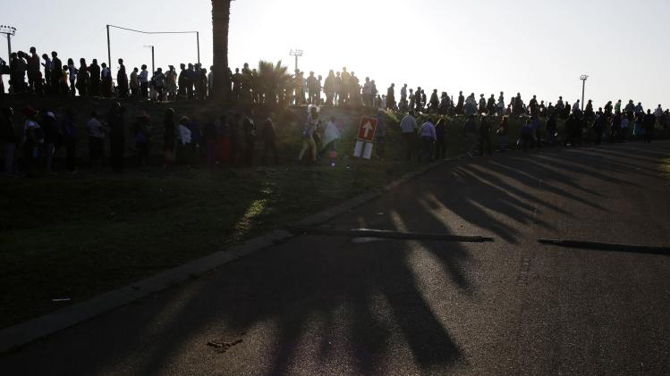 The early morning sun casts shadows from people queuing for buses to pay their respects to former South African President Mandela in Pretoria