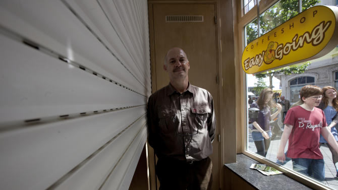 FILE - In this May 1, 2012 file photo owner Marc Josemans poses for a portrait next to the closed shutters inside his coffee shop Easy Going in Maastricht, southern Netherlands. The owners of three cannabis-selling cafes went on trial Wednesday in the southern Netherlands charged with selling weed to foreigners, in a case both sides of a heated drugs debate in this border city hope will clarify the legality of a clampdown on so-called coffee shops. Maastricht is using new legislation banning coffee shops from selling cannabis and marijuana to people who don't live in the Netherlands as a way of clamping down on what the local mayor says was nuisance caused by hundreds of thousands of drug tourists driving into the picturesque heart of the city to stock up on weed. Josemans is a spokesperson for the coffee shops in Maastricht and is expect to go on trial next week. (AP Photo/Peter Dejong, File)