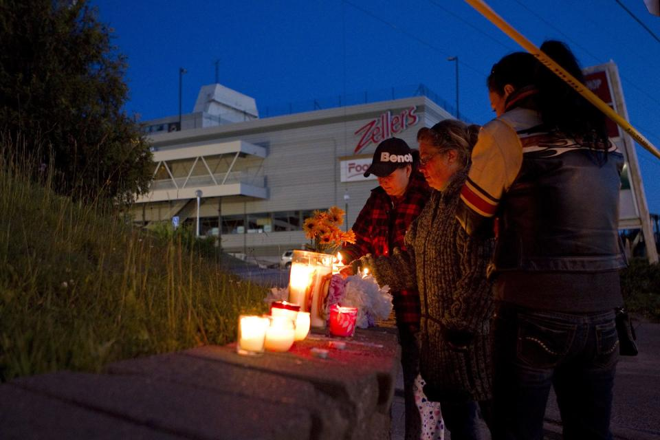 Well wishers leave candles at a vigil as rescue workers continue attempts to secure the building before searching for any survivors at the site of the collapsed roof of the Algo Centre Mall in Elliot Lake, Ontario on Monday June 25, 2012.  (AP Photo/ THE CANADIAN PRESS,Chris Young)