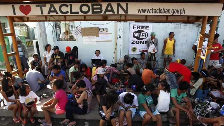 Survivors of super typhoon Haiyan use free internet connection and charge their mobile phone batteries for free at a booth in Tacloban city