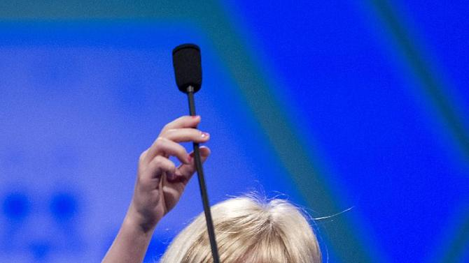 Six-year-old Lori Anne Madison, of Woodbridge, Va., the youngest contestant in the history of the National Spelling Bee, reaches for the microphone during the second round, Wednesday, May 30, 2012, in Oxon Hill, Md.  (AP Photo/Evan Vucci)