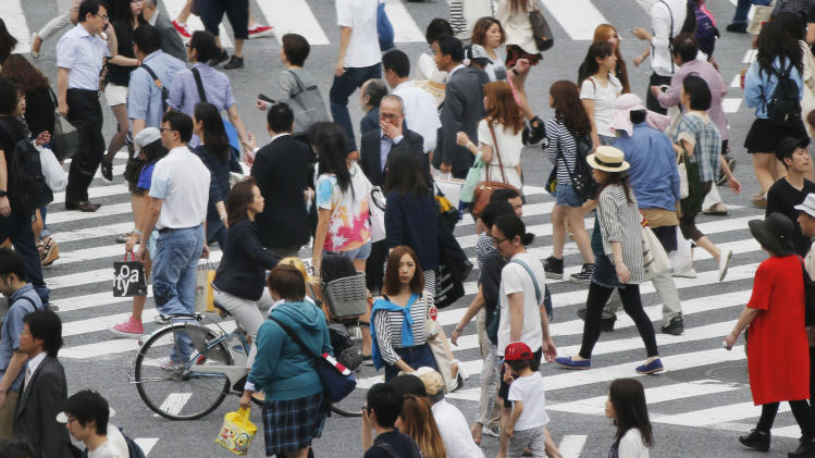"""People cross the street in Tokyo, Monday, July 1, 2013. Business sentiment among major Japanese manufacturers turned positive for the first time in nearly two years, a signal that companies are reacting positively to the weaker yen and Prime Minister Shinzo Abe's policies to revive the stagnant economy. The Bank of Japan's closely-watched quarterly """"tankan"""" survey for June, announced Monday, showed that the index for major manufacturers rose to positive 4 from negative 8 in March. (AP Photo/Koji Sasahara)"""