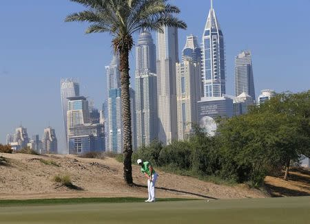 McIlroy of Northern Ireland putts on the third green during the Dubai Desert Classic
