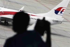 A passenger takes pictures of Malaysia Airlines plane at Kuala Lumpur International Airport