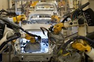 Volkswagen Tiguan and Touran models are being welded by robots at the assembly line in Wolfsburg, central Germany. German industrial output declined in June, as the debt crisis increasingly makes itself felt on Europe's biggest economy