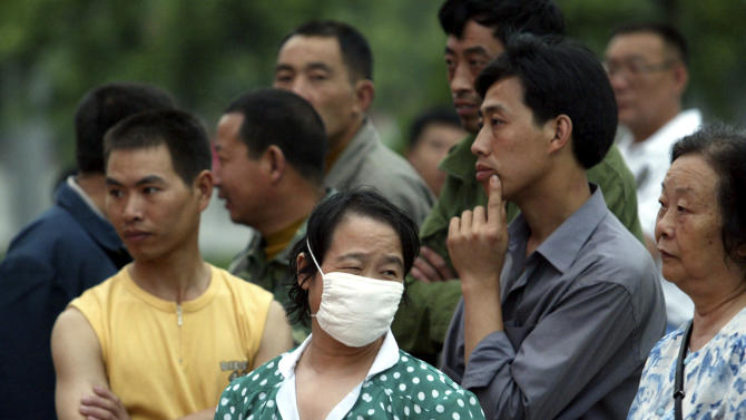 FILE - In this Sunday, June 8, 2003 file photo, a masked Chinese woman reacts as she stands in a crowd on the streets of Beijing, China. A genetic variant commonly found in Chinese people may help explain why some patients got seriously ill with swine flu, a discovery scientists say could help pinpoint why flu viruses hit some populations particularly hard and change how they're treated. Less than one percent of Caucasians are thought to have the gene alteration, which has previously been linked to severe influenza. About 25 percent of Chinese have the gene variant, which is also common in Japanese and Korean people. (AP Photo/Ng Han Guan, File)