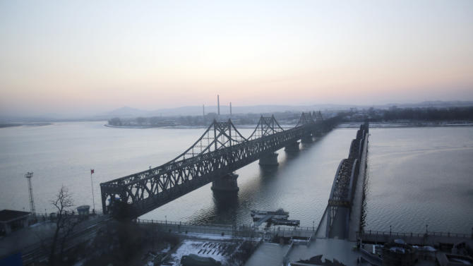 In this Feb. 7, 2013 file photo, the Friendship Bridge, left, linking China and North Korea, and the Yalu River Bridge, right, which was bombed in the 1950's during the Korean War, are seen before daybreak in Dandong, China, opposite the North Korean border town of Sinuiju. China's patience with North Korea is wearing thin, and a widely-expected nuclear weapons test by the latter could bring that frustration to a head. Beijing signaled its growing unhappiness by agreeing to tightened U.N. sanctions after North Korea launched a rocket in December, eliciting harsh criticism from Pyongyang and comment from China watchers surprised by Beijing's unusually tough line. (AP Photo/Eugene Hoshiko)