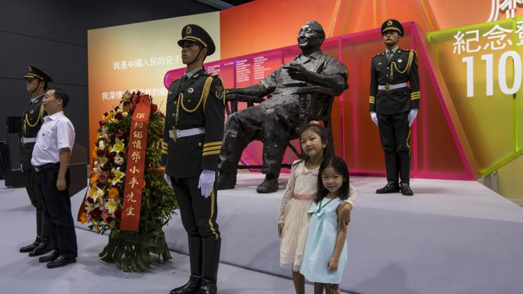 People pose next to soldiers of the People's Liberation Army (PLA) in front of a statue of the late Chinese leader Deng Xiaoping, at an exhibition commemorating the 110th anniversary of his birth, in Hong Kong