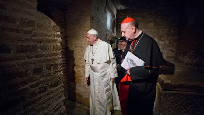 """FILE - In this April 1, 2013 file photo made available by the Vatican newspaper L'Osservatore Romano, Pope Francis, followed by Cardinal Angelo Comastri, right, visits the necropolis where pagans and early Christians were buried under St. Peter's Basilica at the Vatican and where St. Peter is believed to be buried. The Vatican's decision to publicly exhibit the purported relics of the Apostle Peter for the first time this weekend has spotlighted the intense scientific debate over whether the bones actually belong to the first bishop of Rome. No Pope has ever definitively declared the bones to be Peter's, though Pope Paul VI in 1968 said fragments found in the necropolis under St. Peter's Basilica were """"identified in a way that we can consider convincing."""" Some Vatican archaeologists disagreed, and debate continues today much as it has over the authenticity of the Shroud of Turin. (AP Photo/L'Osservatore Romano, file, ho)"""