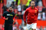 Manchester United's English defender Rio Ferdinand (R) warms up without wearing an anti-racism Kick It Out T-shirt, before his team's English Premier League football match against Stoke at Old Trafford in Manchester, north-west England