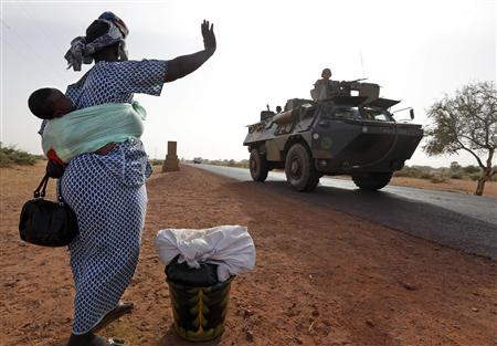 A woman waves to French soldiers, which is part of a convoy of French military vehicles including armored personnel carriers, jeeps and supply trucks, heading toward the recently liberated town of Diabaly January 24, 2013. REUTERS/Eric Gaillard