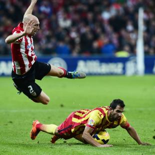 Athletic Bilbao's Gaizka Toquero falls over Barcelona's Martin Montoya during their Spanish first division soccer match at San Mames stadium in Bilbao