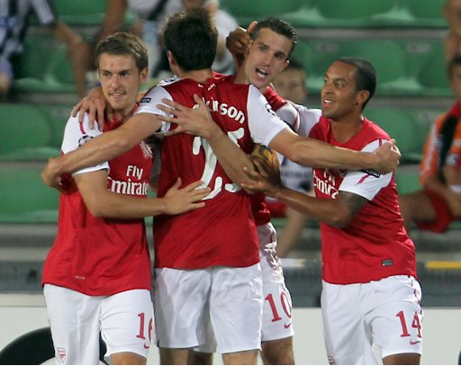 Arsenal's Robin Van Persie, center, celebrates with teammates Aaron Ramsey, left, Carl Jenkinson (back to camera) and Theo Walcott, right, after scoring against Udinese during a Champions League qualifying playoff second leg soccer match in Udine, Italy, Wednesday, Aug. 24, 2011. Arsenal won 2-1 and advances 3-1 on aggregate. (AP Photo/Paolo Giovannini)
