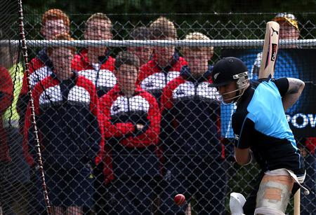 New Zealand cricket team player McCullum bats in the nets as he is watched by school children during a training session at the University Oval in Dunedin