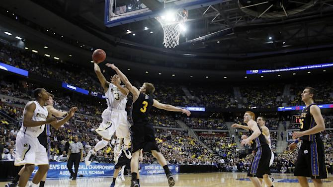 Michigan guard Trey Burke, center left, takes a shot against South Dakota State guard Nate Wolters during the first half of a second-round game of the NCAA men's college basketball tournament Thursday, March 21, 2013, in Auburn Hills, Mich. (AP Photo/Duane Burleson)