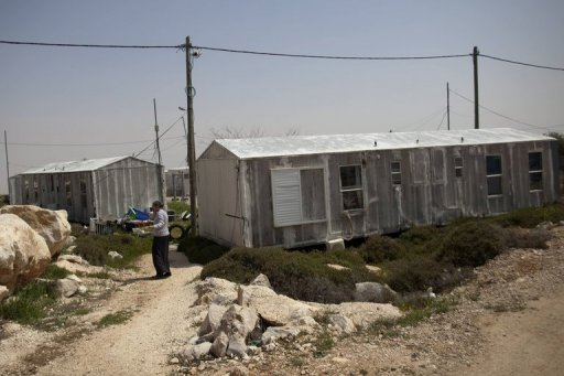 An Israeli settler woman walks outside her prefabricated house in the Jewish settlement of Migron in the occupied West Bank in March 2012. Israel on Sunday again asked the Supreme Court for more time to evacuate the Migron settlement outpost, which the same court has ordered razed by August 1