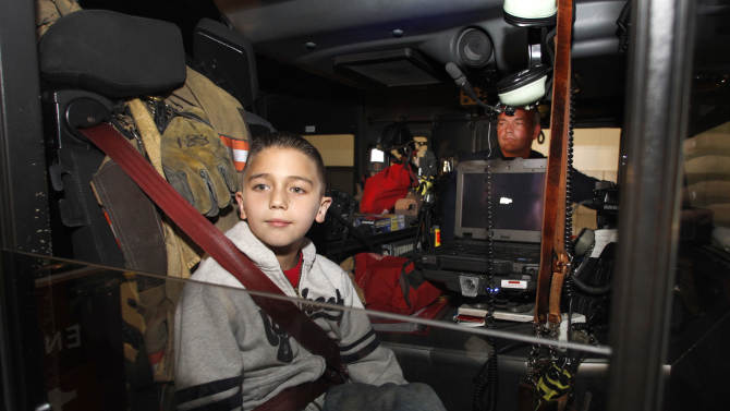 Koregan Quintanilla, 10, of Watauga, Texas, looks out the passenger window of a Arlington Fire Department fire truck as firefighter Wesley Keck, rear, prepares to take him on a short trip around the neighborhood Thursday, Nov. 15, 2012, in Arlington, Texas. Quintanilla, who was abandoned at a fire station as an infant, celebrated his recent birthday by meeting Keck, the firefighter who saved him, riding on a fire truck and touring the station. (AP Photo/Tony Gutierrez)