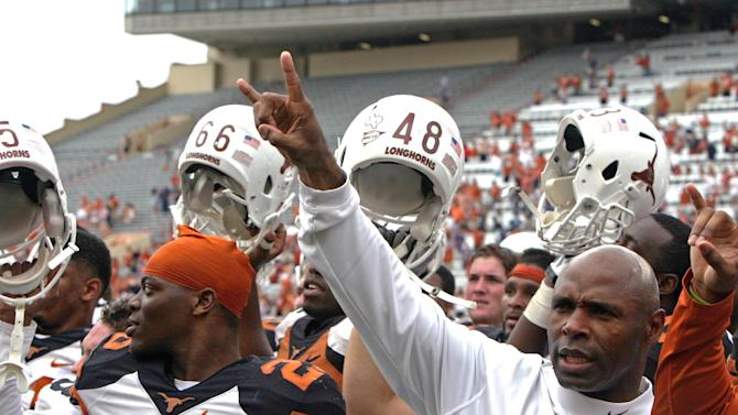 "Texas coach Charlie Strong gives the ""hook 'em horns"" sign while his players raise their helmets after the Orange and White spring NCAA college football game, Saturday, April 19, 2014, in Austin, Texas"