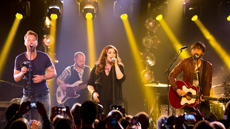 FILE - This May 8, 2013 file photo released by iHeartRadio shows members of the band Lady Antebellum, from left, Charles Kelley, Hillary Scott, and Dave Haywood during a performance in New York. Lady Antebellum is postponing the start of its 60-date concert tour. The Nashville, Tenn.-based country music trio says it will now begin the 60-plus city tour Jan. 10 in Peoria, Ill. Lady A had been scheduled to start the tour Nov. 8 in Omaha, Neb., and 17 shows will be rescheduled. (AP Photo/iHeartRadio, Chris Owyoung, File)