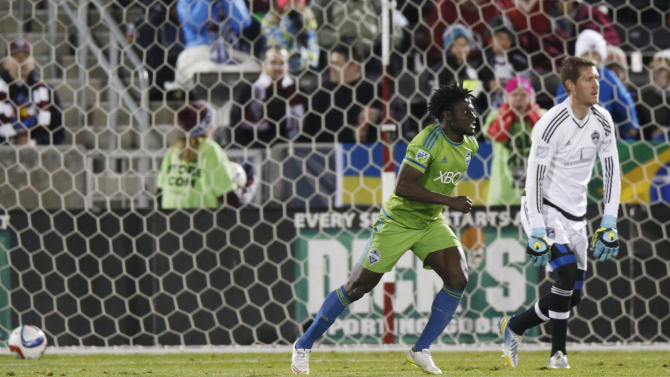 Seattle Sounders forward Obafemi Martins, front, runs away after his goal past Colorado Rapids goalie Clint Irwin during the second half of an MLS soccer game Saturday, April 18, 2015, in Commerce City, Colo. Seattle won 3-1. (AP Photo/David Zalubowski)