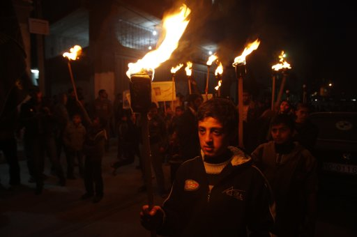 Palestinian boys hold torches during a protest in the central Gaza Strip
